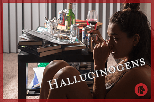 woman sitting in corner with drugs and alcohol on table nearby