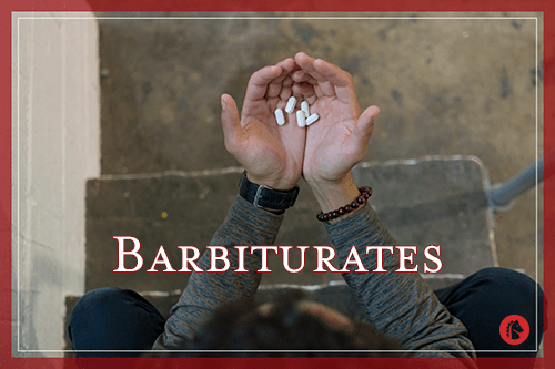 man holding pills of barbiturates