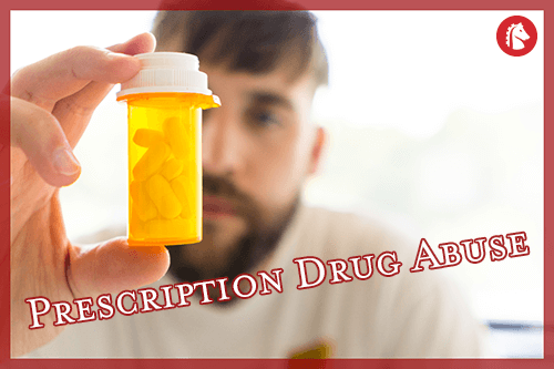 man holding and staring at a bottle of prescription pills