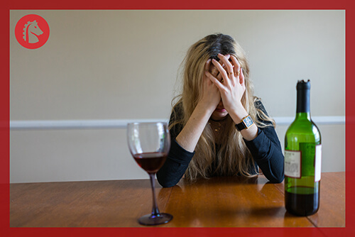 woman with hands on head because of alcohol withdrawal