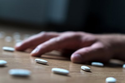 Pills spilled on table with hand of addict