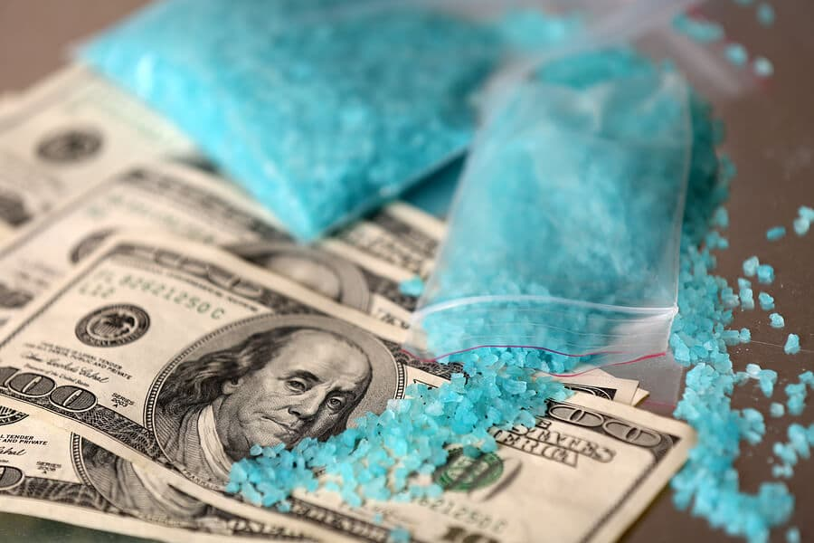 Opened bag of crystal meth pour on hundred dollar bills