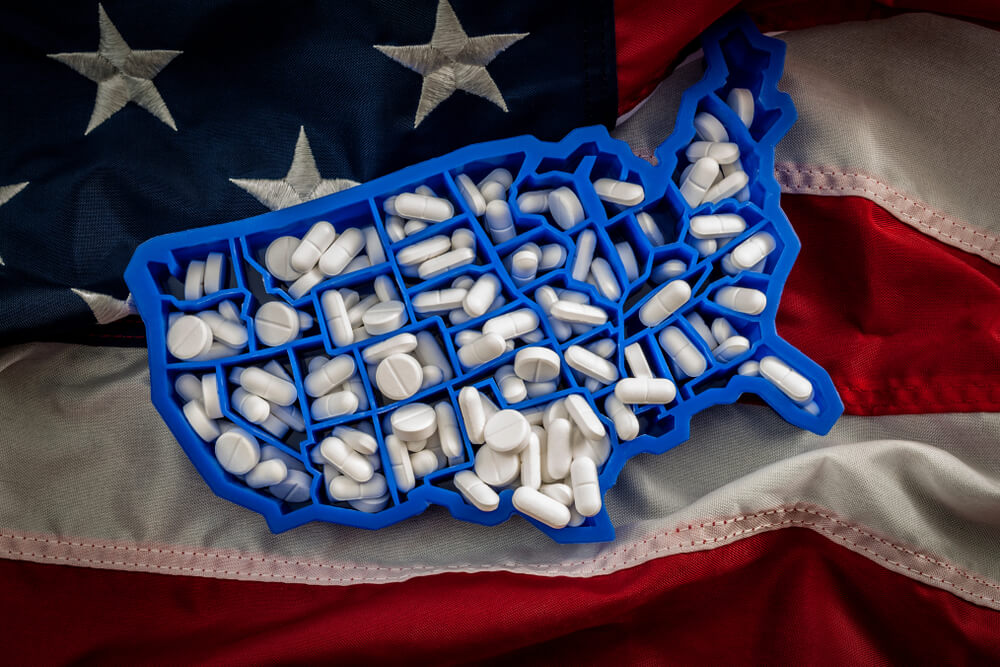 USA shaped pill holder full of pills sitting on american flag
