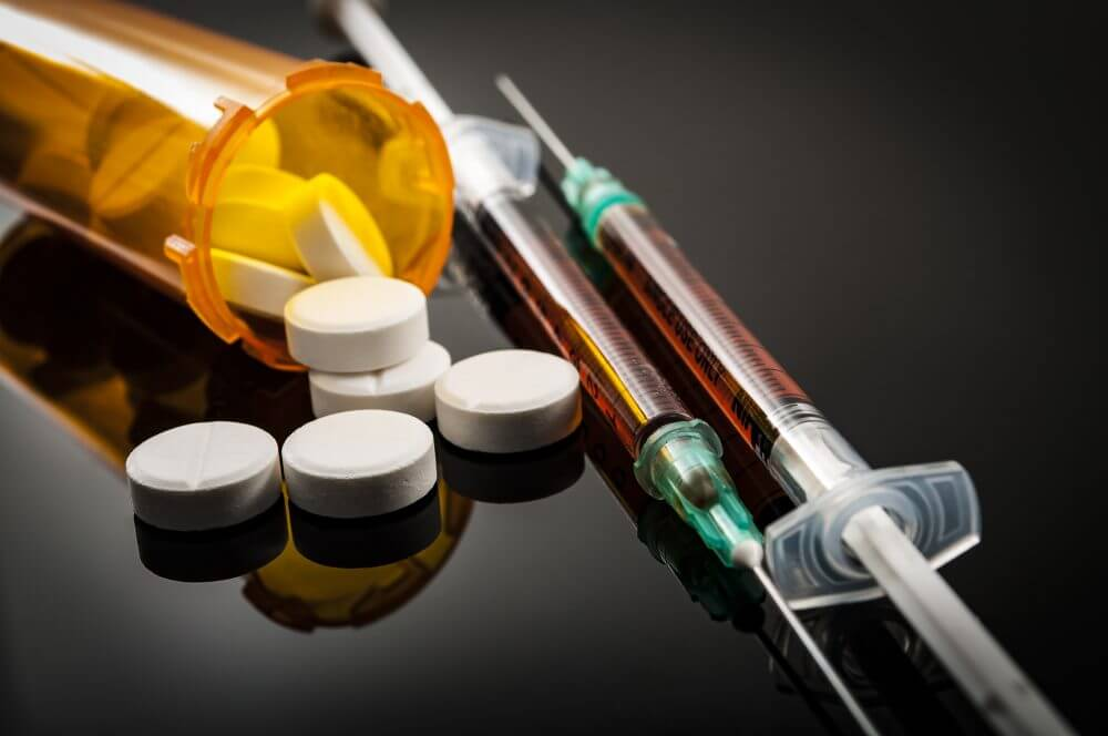 pill bottle of opioids next to syringes with heroin
