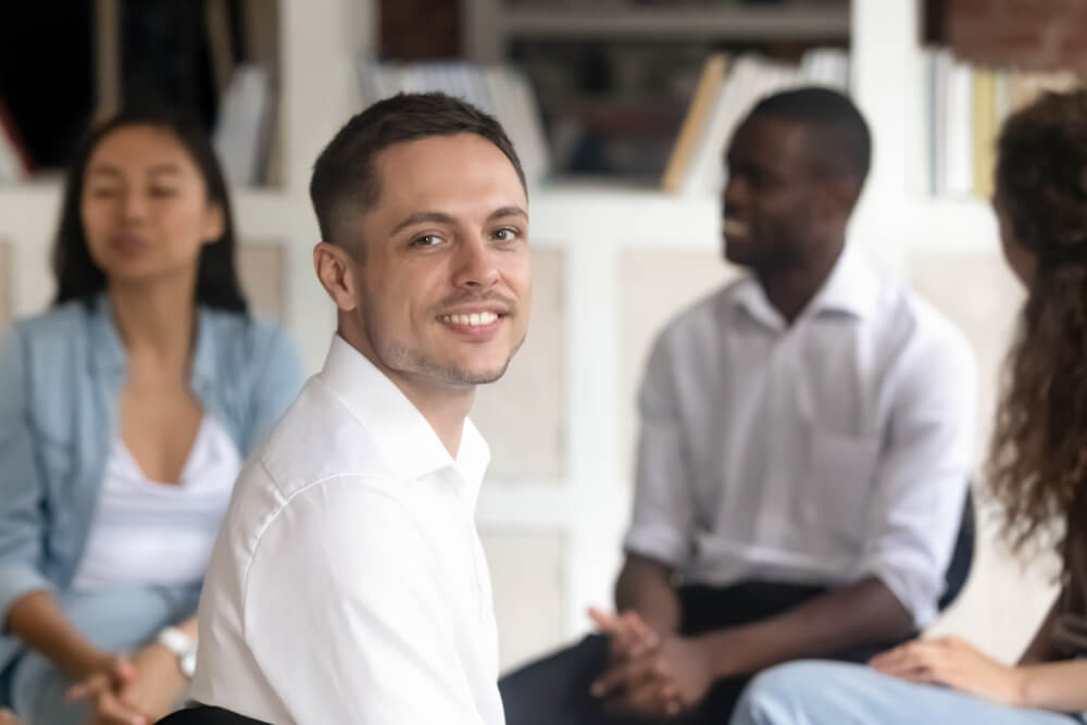 man smiling in group therapy